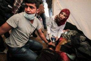 Razan al-Najjar works with a colleague to tend to an injured man at an emergency medical tent in the southern Gaza Strip.