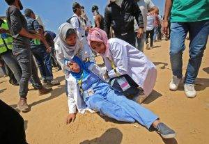 Razan helps an injured colleague on May 15. Photo courtesy of Said Khatib/AFP